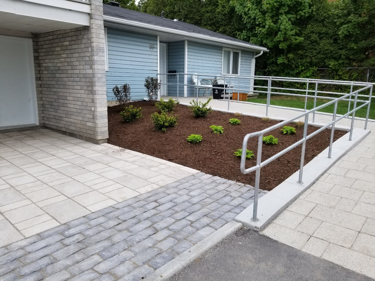Plant bed, concrete ramp with handrail, and precast concrete pavers at Marlborough Towers