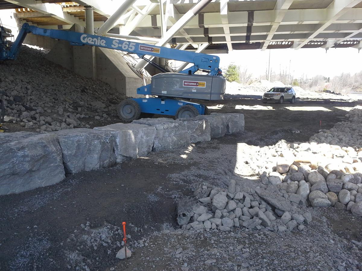 Stone retaining wall under abutment of Strandherd Armstrong Bridge