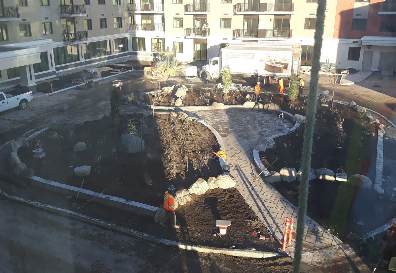 Construction of plaza with plant beds, decorative boulders, precast concrete pavers, and planting at Les Terasses Francesca Apartment Community