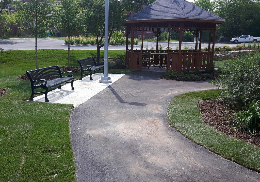 Asphalt path, benches, and soft landscaping at Grace Manor