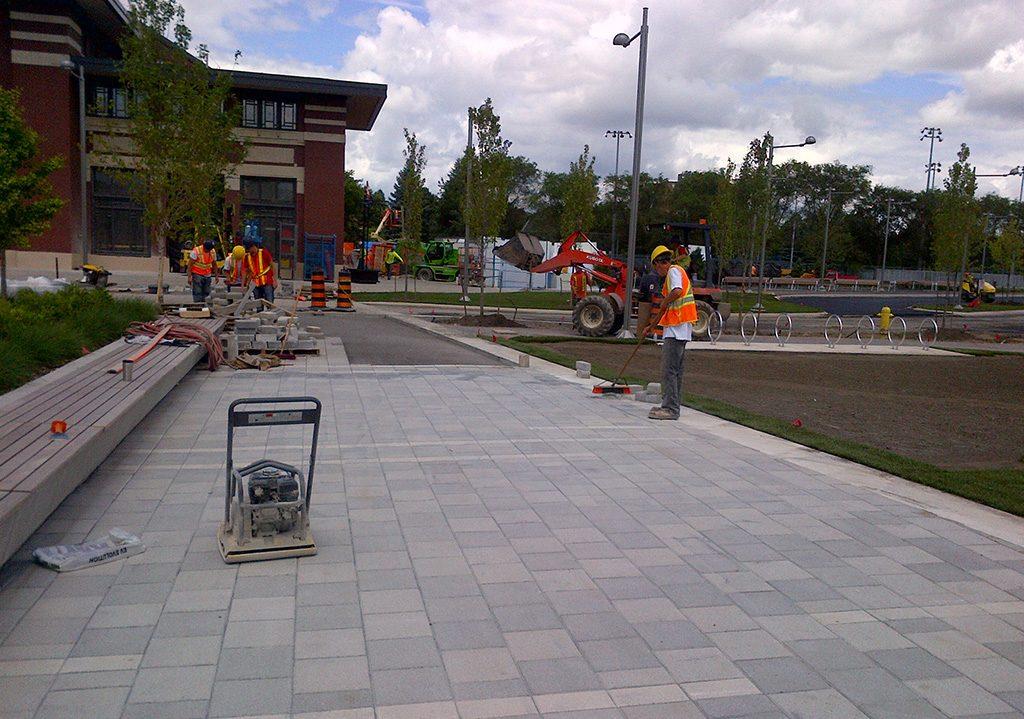 Hard landscaping crew installing precast concrete pavers at Lansdowne Park